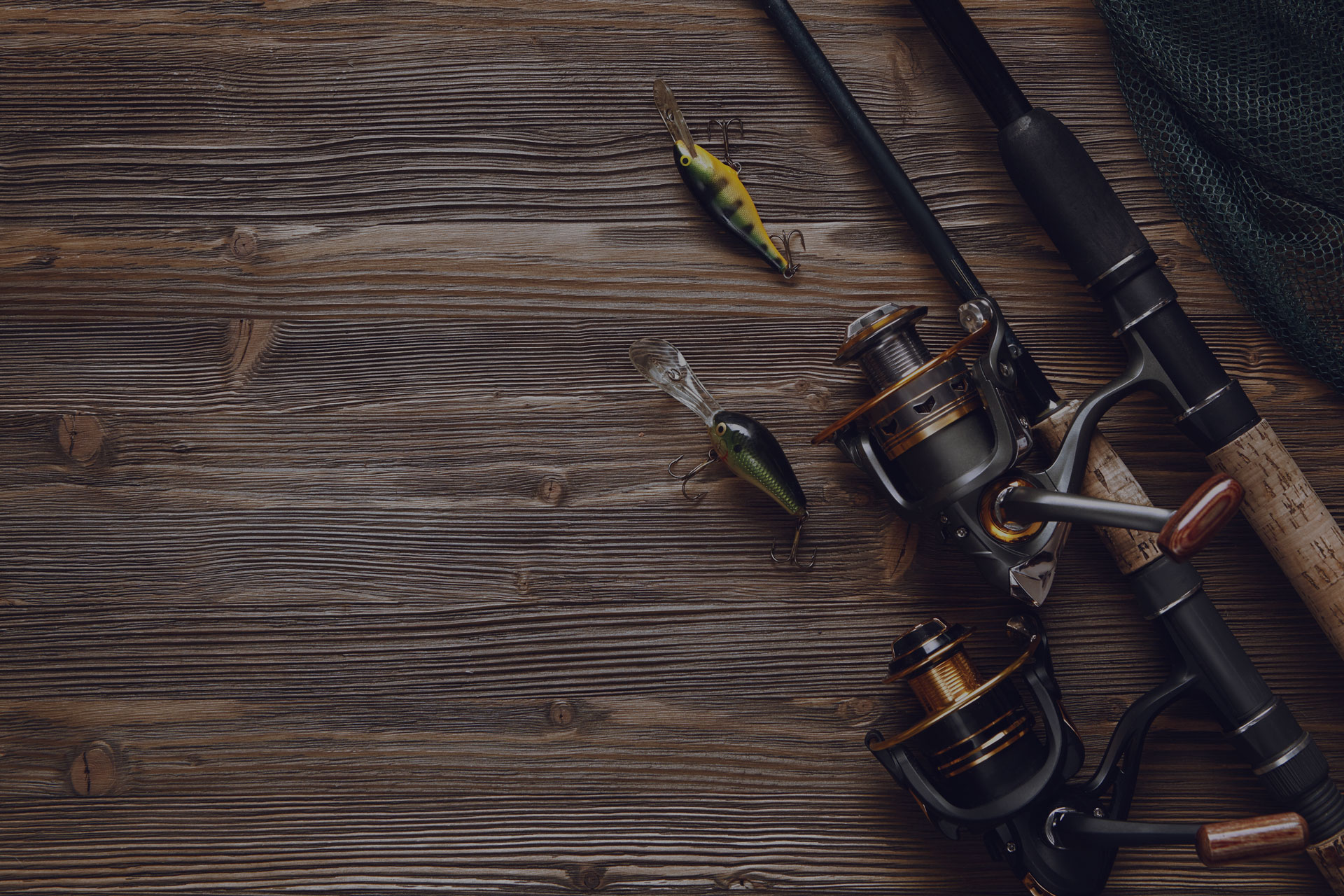 Fishing tackle - fishing spinning, hooks and lures on darken wooden background